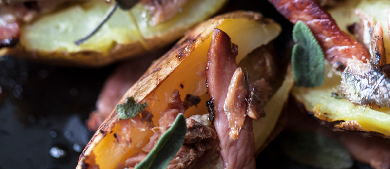 Baked potatoes with bacon, anchovies and sage